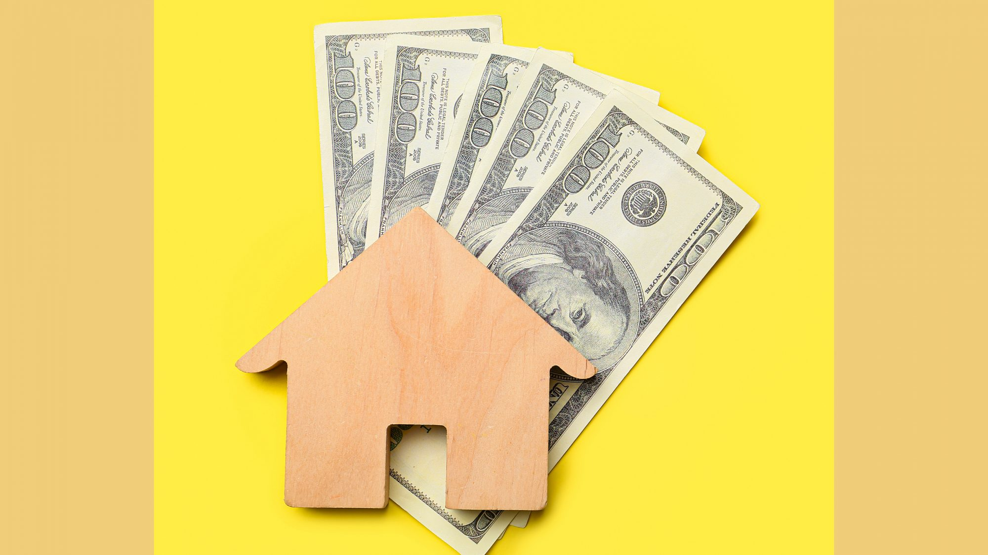 Figure of house with dollar banknotes on color background