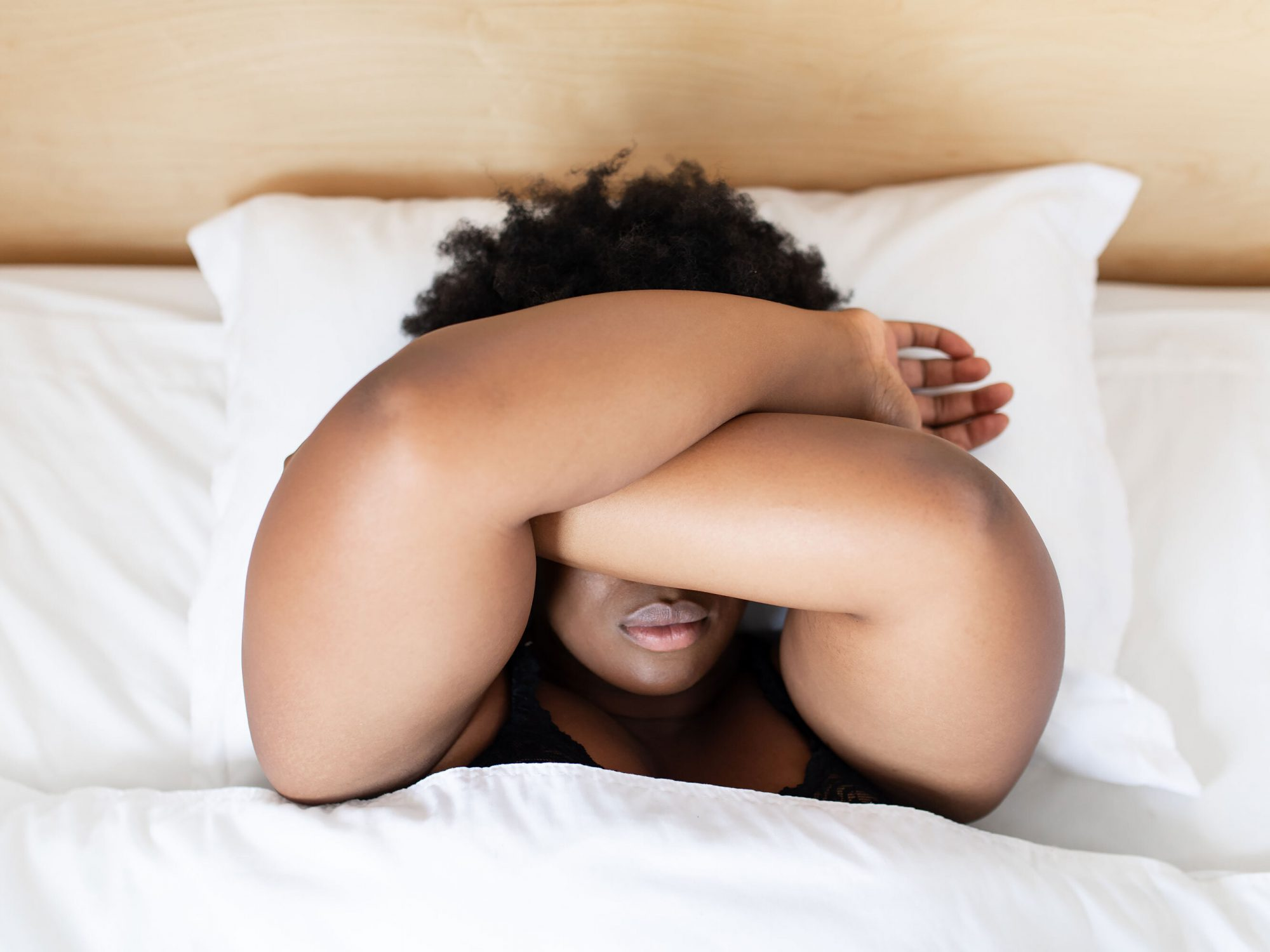 woman lying in bed with arms over her eyes