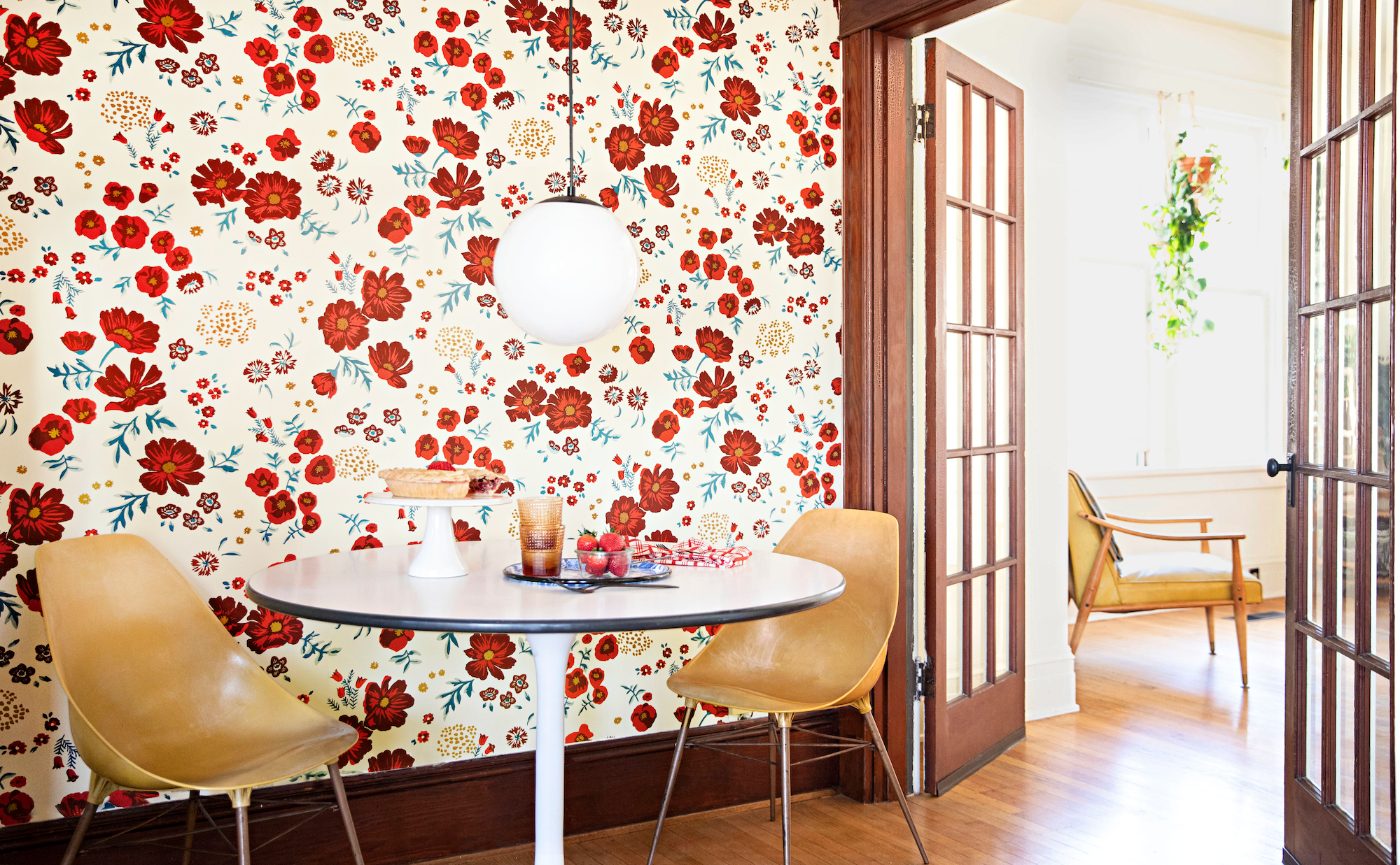 red floral wallpaper and midcentury furniture in dining area