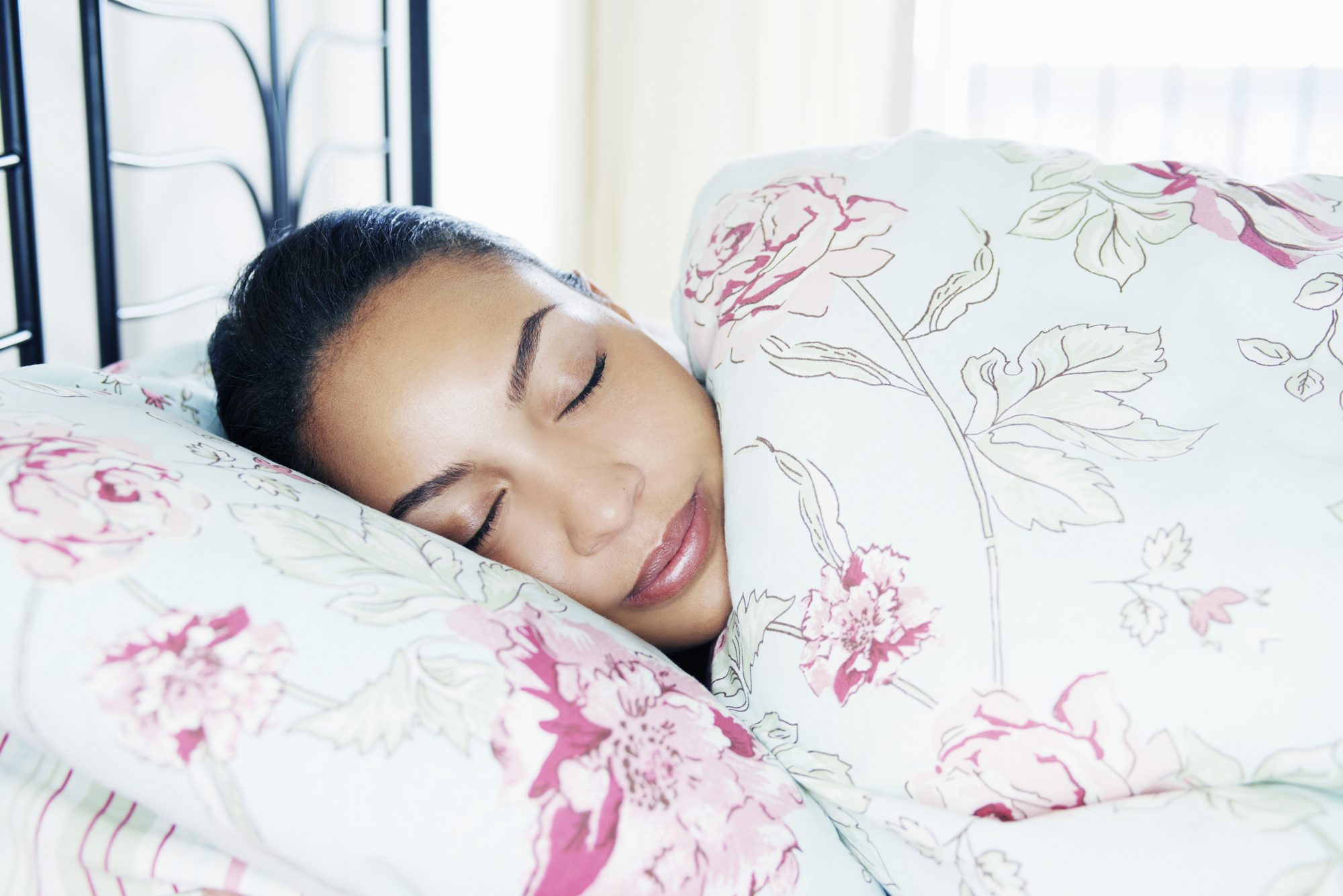 portrait of young woman asleep in bed