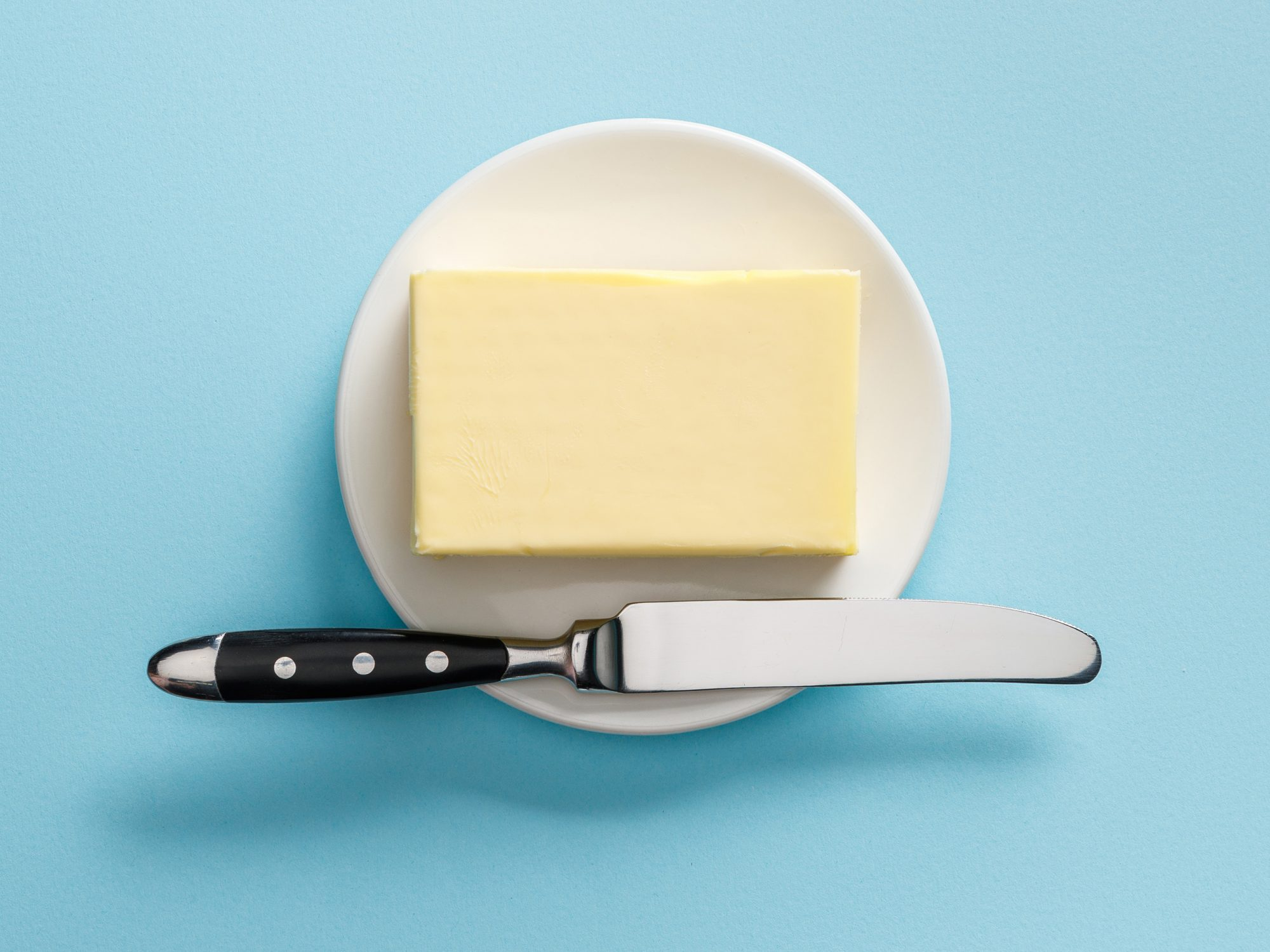 top view of butter and knife on white plate on blue background