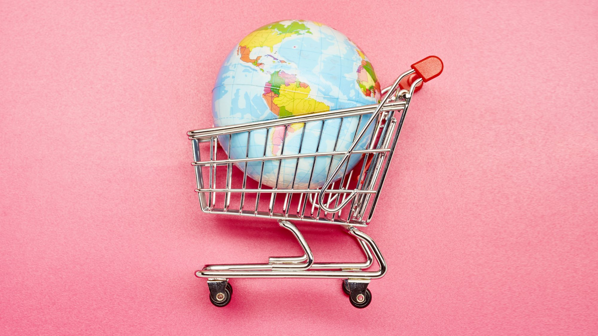 A small shopping cart with planet earth in it