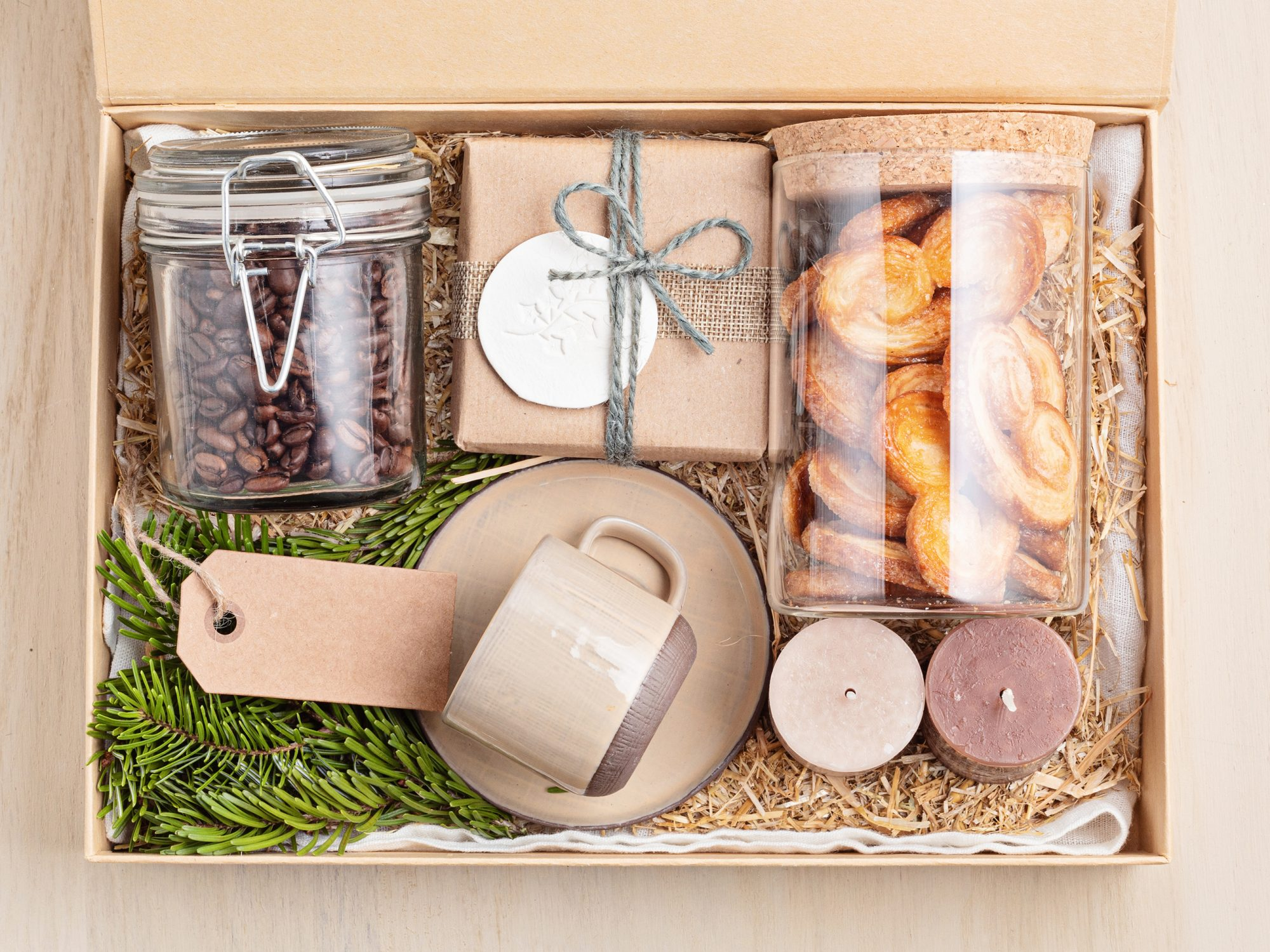 Preparing care package, seasonal gift box with coffee, cookies, candles and cup