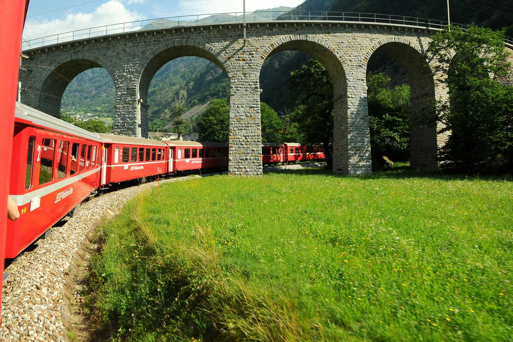 Swiss Red Train Bernina Express pass on Brusio Viaduct. It is a spectacular helicoidal stone bridge that fits the surrounding landscape and is located on the Bernina railway not far from Brusio railway station in Canton Grisons, Italy.