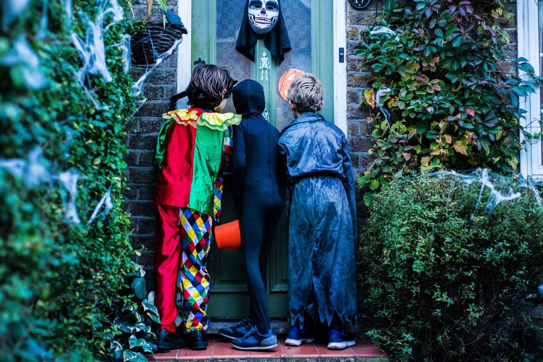 Three boy in halloween costumes, standing at door, trick or treating, rear view