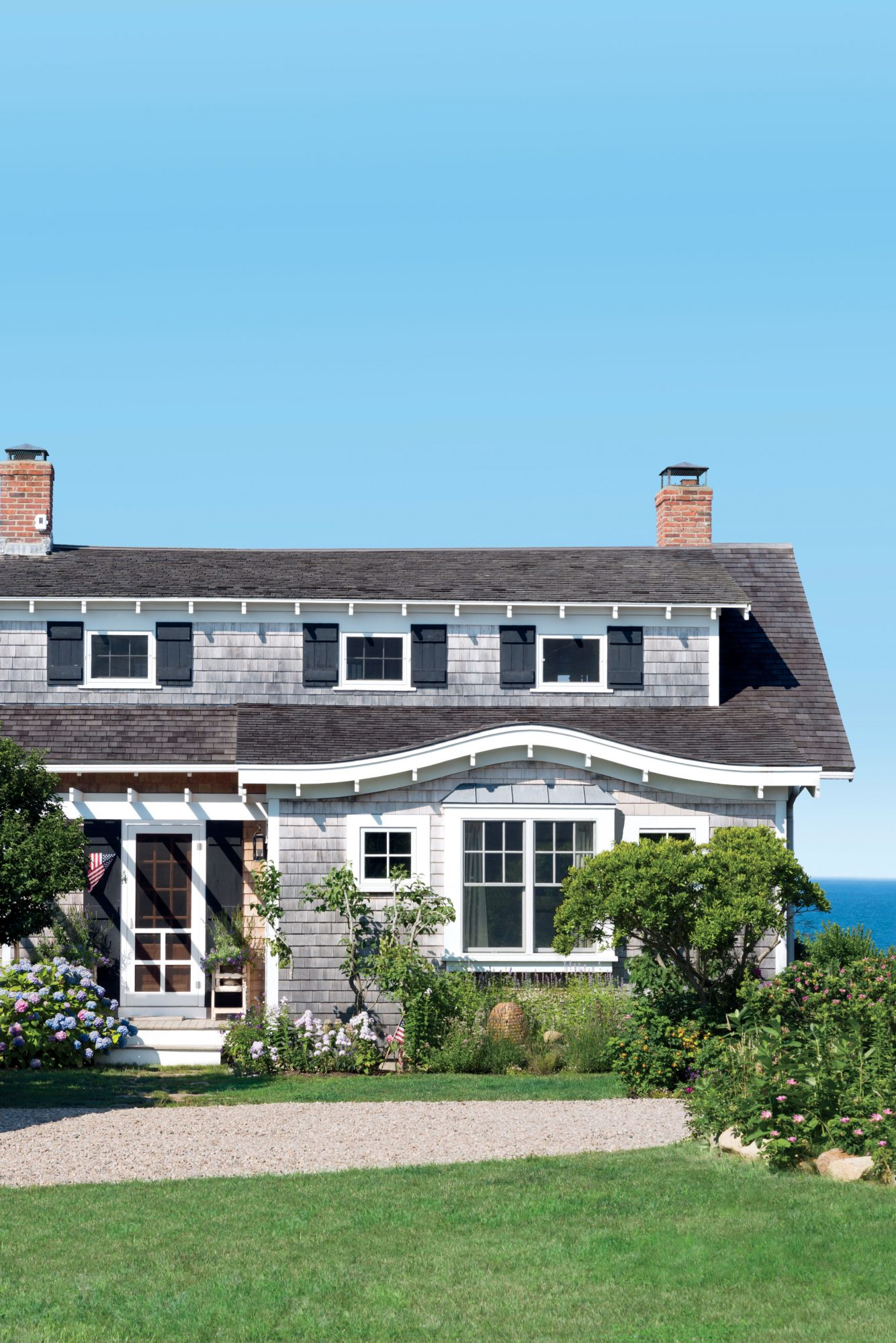 Cape Cod-style beach cottage in Orleans, Massachusettes with gray shingles, black shutters, and a water view.
