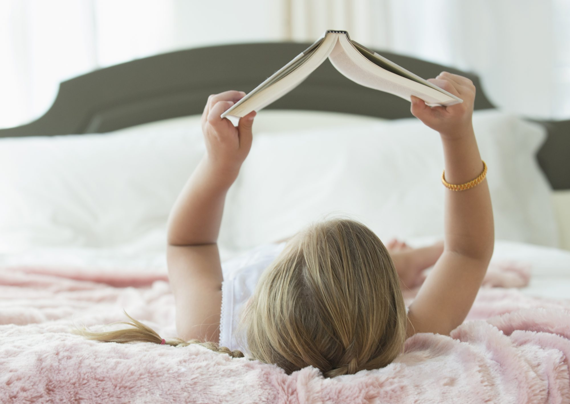 Caucasian girl laying on bed reading book