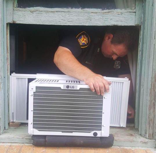 police officer gives air conditioner to ninety-five year old man