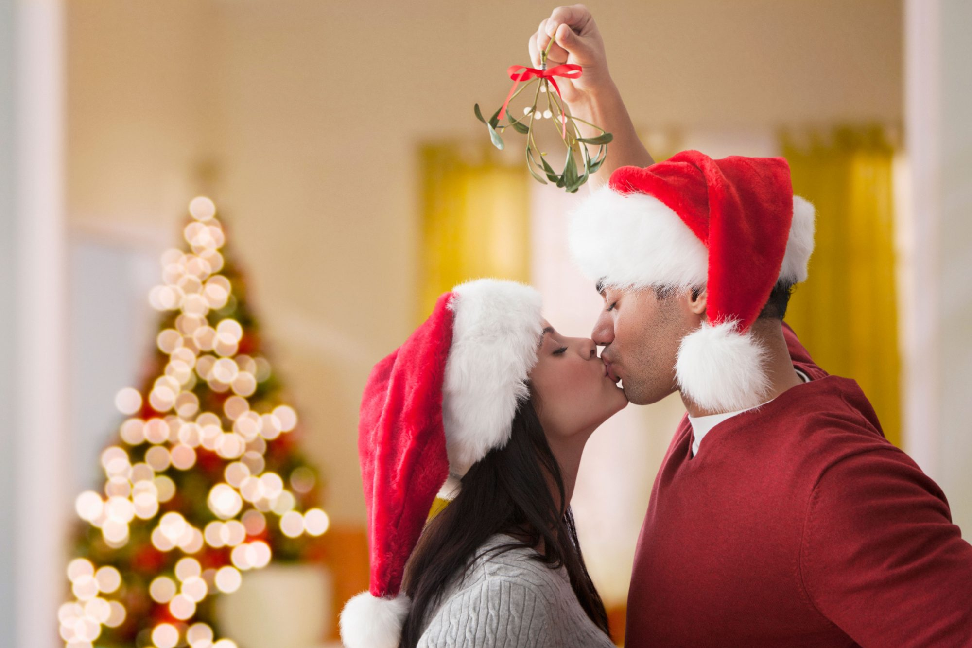Couple Kissing Underneath Mistletoe at Christmas