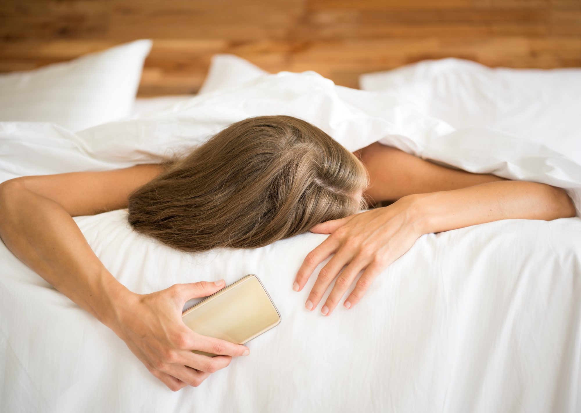 Woman Sleeping in Bed Holding Phone