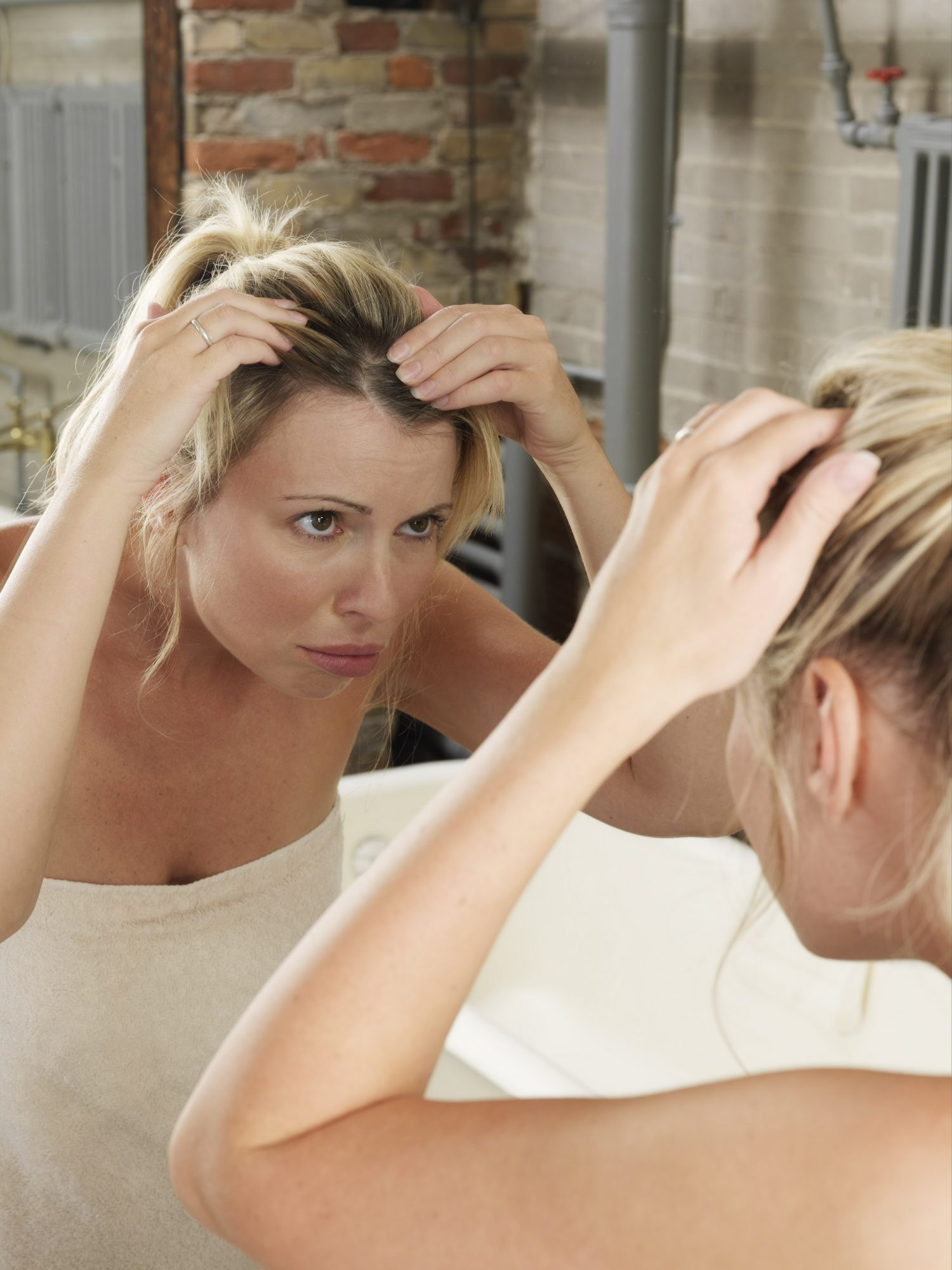 Woman In Bathroom Looking In Mirror at Hair Roots