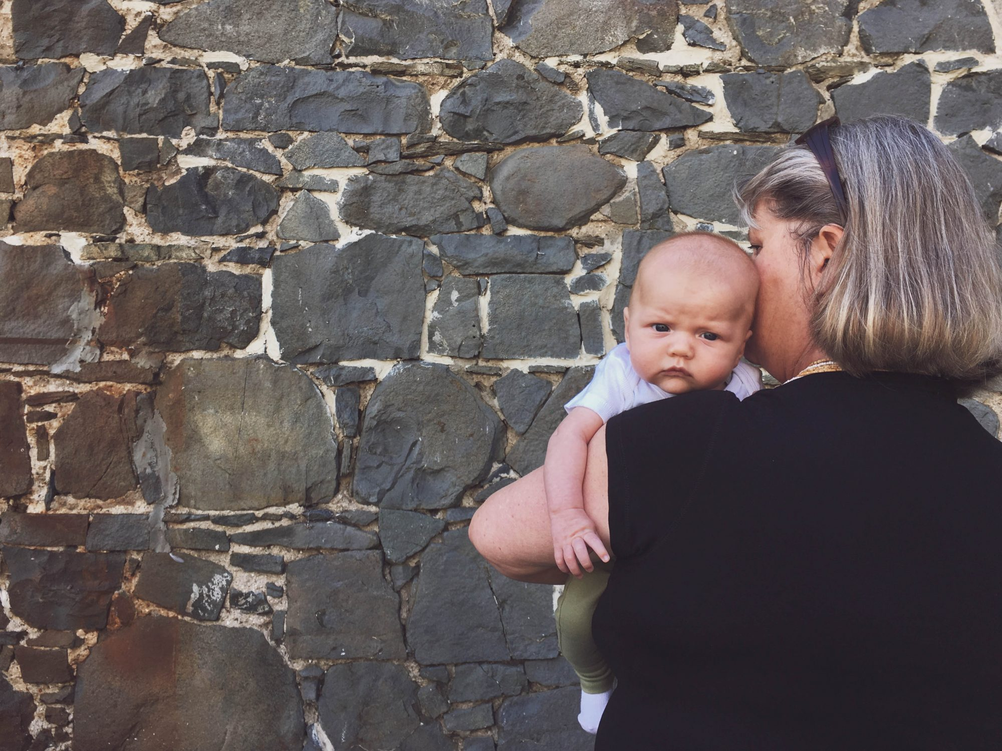 Grandmother Holding Baby Stone Wall