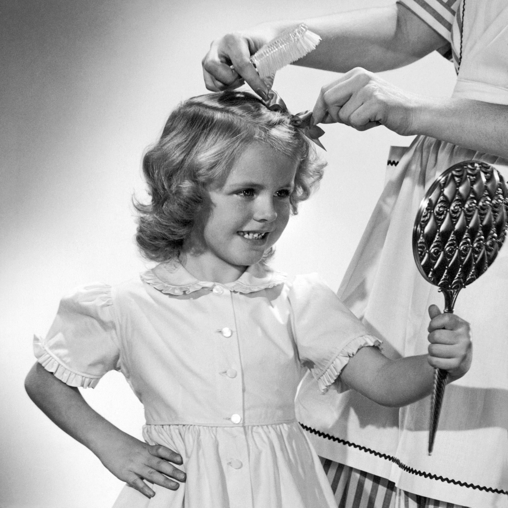 Mother Putting Bow in Daughter's Hair