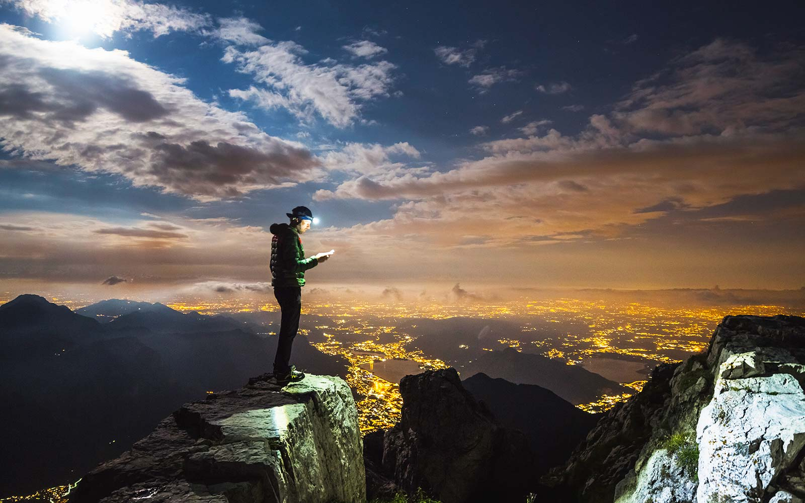 Hiker on top on the mount, full moon and city illuminated