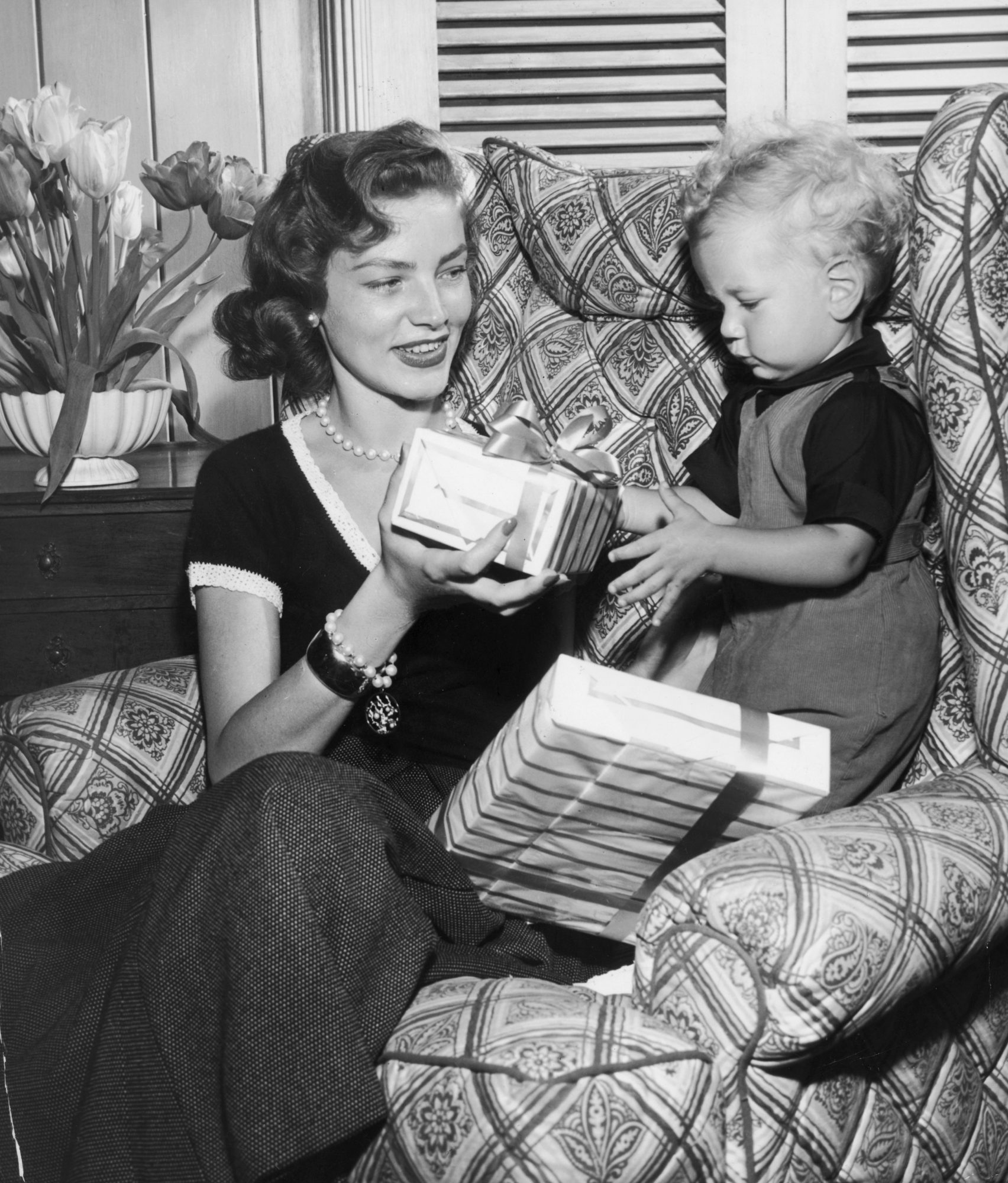 mother handing gift to child