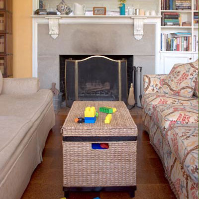 two mis-matched couches face each other with a wicker coffee table in front of a fireplace with a brass heat protector