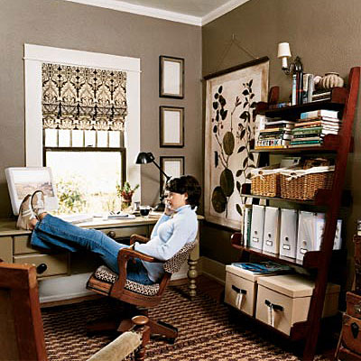 A desk is positioned in front of the window in this home office, while ladder shelving with decorative storage containers are organized on the opposite wall. Chocolate brown walls and black, brown and cream window treatment completes the look of this work