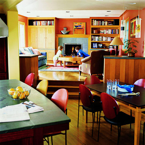 bright, vibrant colors and natural wood used in the kitchen area extend into the remodeled and expanded family room
