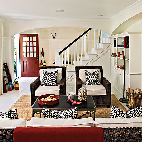 white walls and cabinets in the living room highlight black and white patterned pillows on the arm chairs, with a  red throw set behind the couch