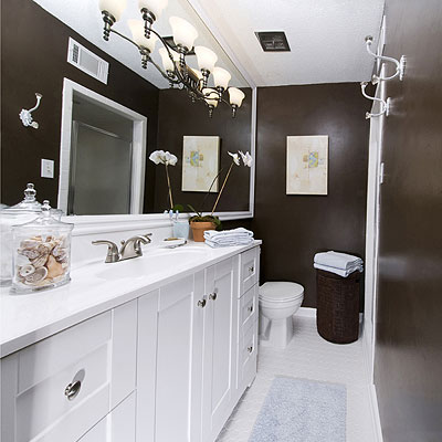 deep chocolate walls of this renovated bathroom offset the crisp, white bathroom cabinets and the large, expansive bath mirror with a light fixture