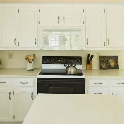 white kitchen cabinets, microwave, and kitchen island with neutral colored accents in the kitchen accessories