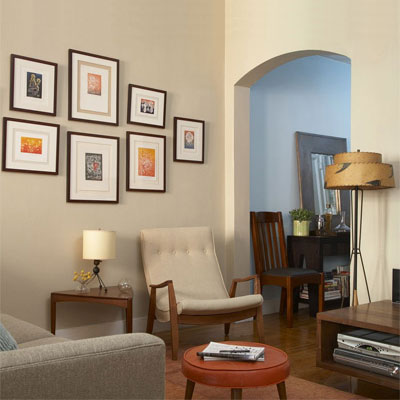 living room with mid-century furniture, lamps and arm chair with framed art on the light cream walls