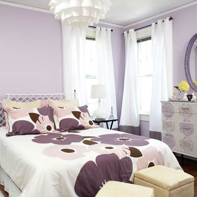 In the master bedroom, purple flowered bedspread with pale purple walls, white curtains and a white, modern chandelier