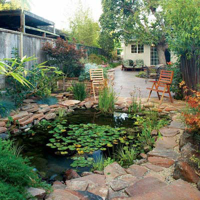 backyard lily pond surrounded by stones with a couple of lawn chairs positioned at the edge