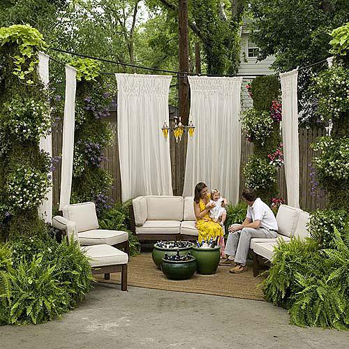 Tall white drapes are hung around the driveway space with a loveseat with cotton cushions and side chairs arranged in a u-shape to create an outdoor room. Ferns in containers and other hanging flowers are hung throughout the space.