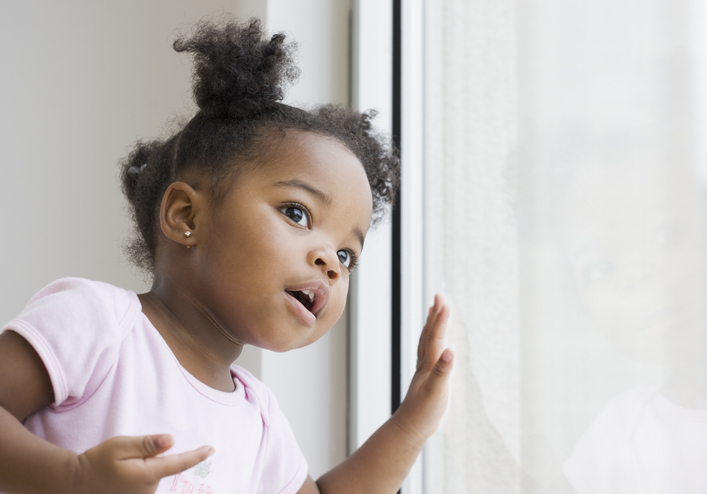 African American girl looking out window