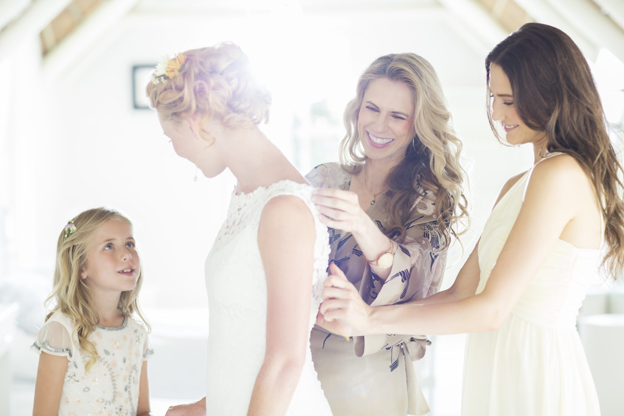 Bridesmaids helping bride with her dress on wedding day