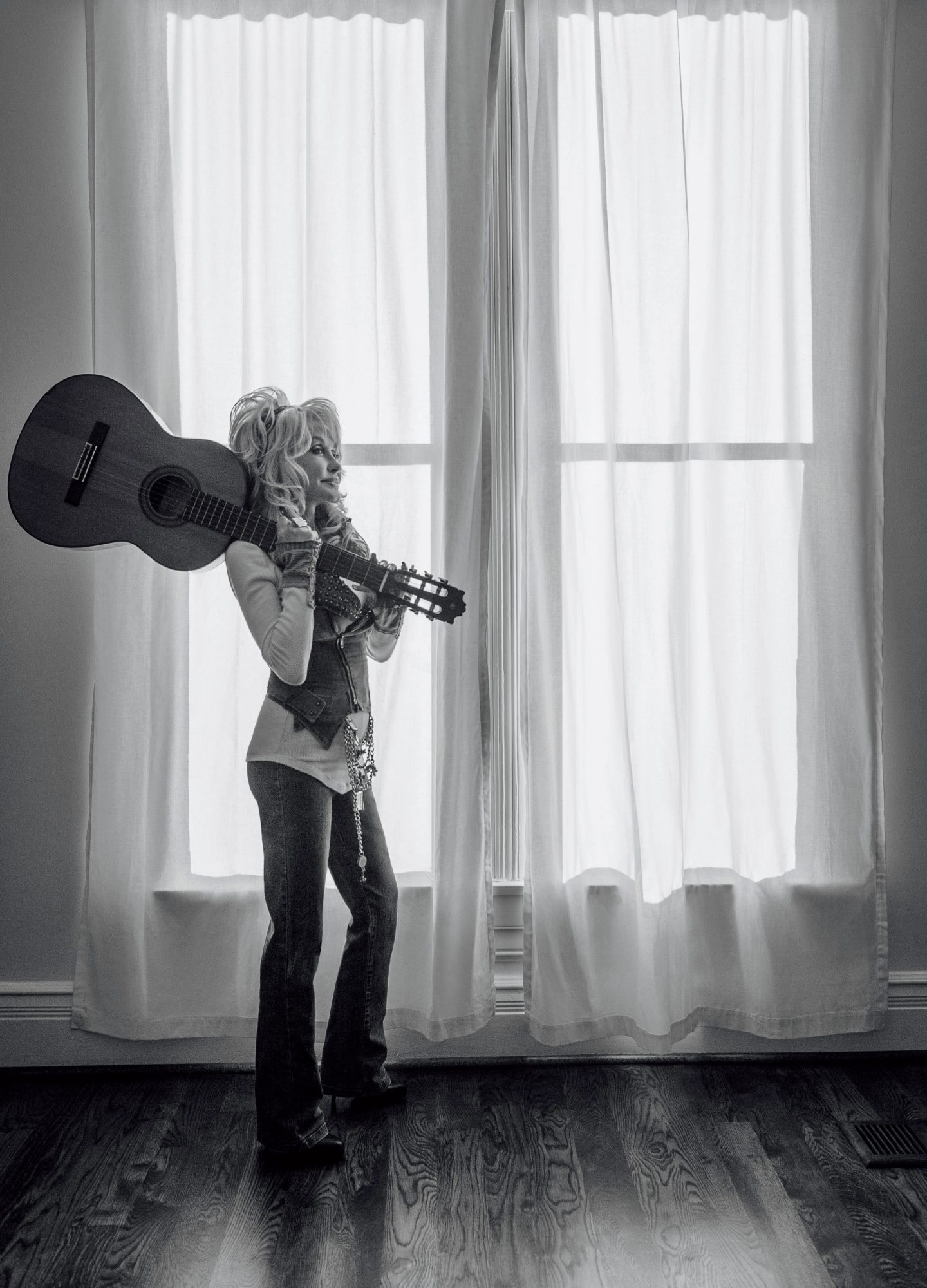 Dolly Parton holding a guitar over her shoulder