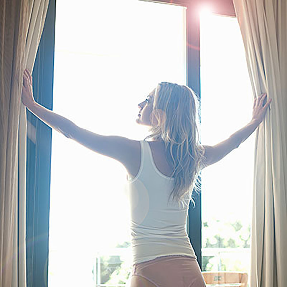 Woman Opening Shades to Sunlight
