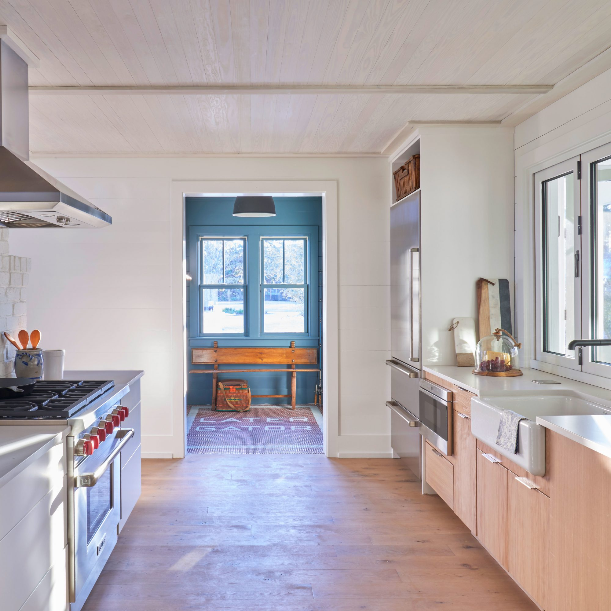 A kitchen with light wood floors, custom cabinetry, and concrete countertops in a contemporary Lowcountry home.