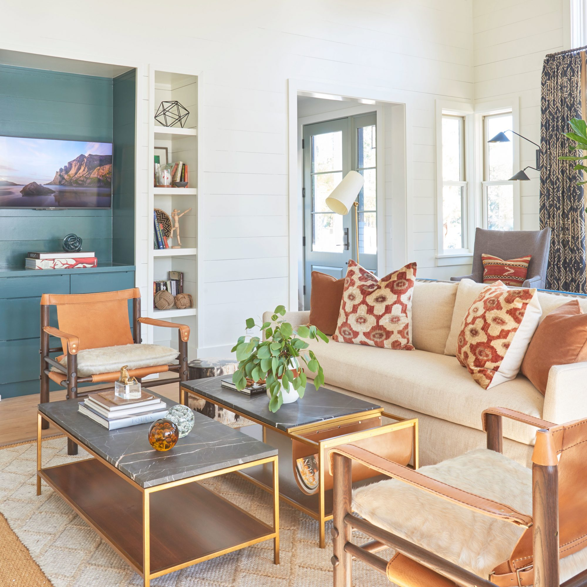 A living room with light wood floors, white shiplap walls, a teal recess, and bronze, wood, and leather furnishings in a contemporary Lowcountry home.