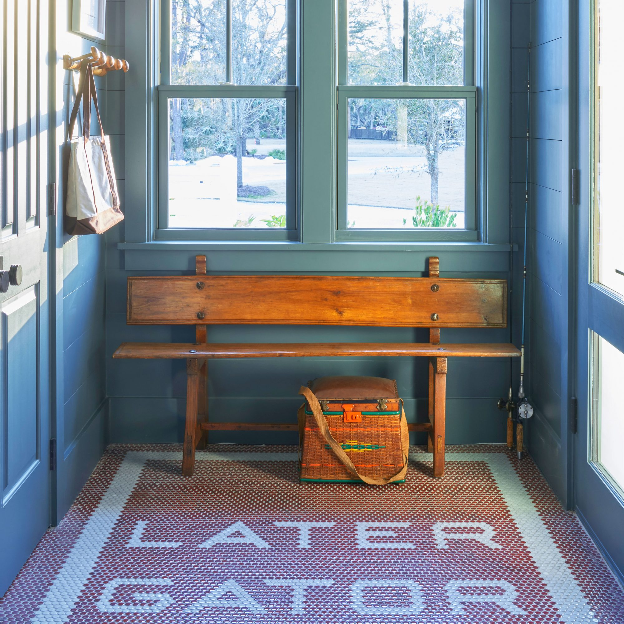 A mudroom with custom penny tiling and teal walls in a contemporary Lowcountry home.