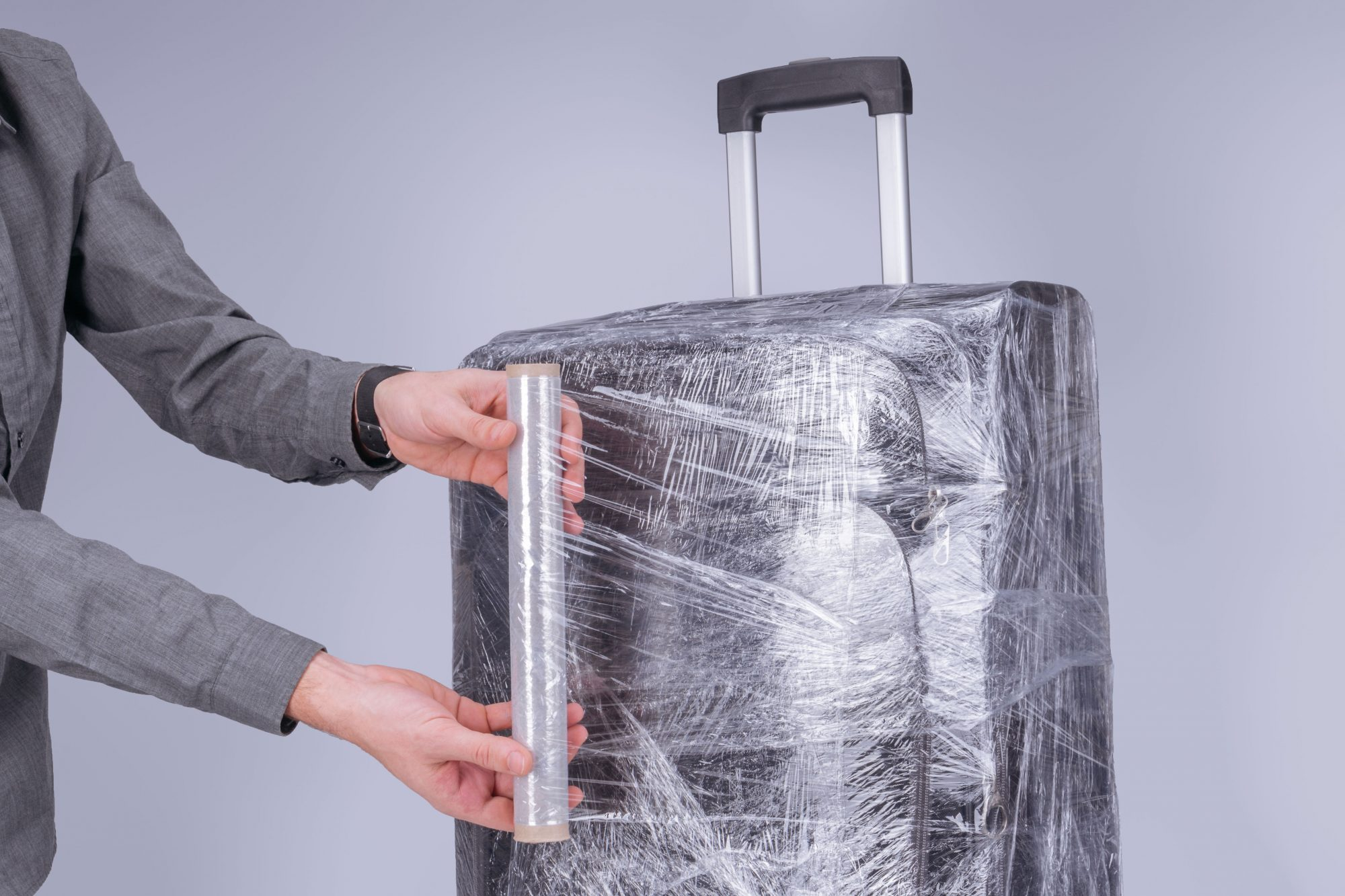 Wrapping Suitcase in Plastic