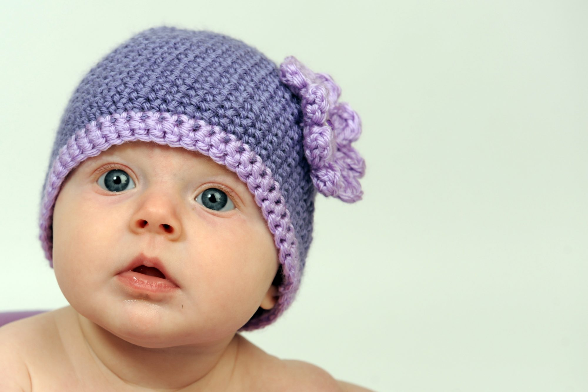 baby wearing purple knit hat