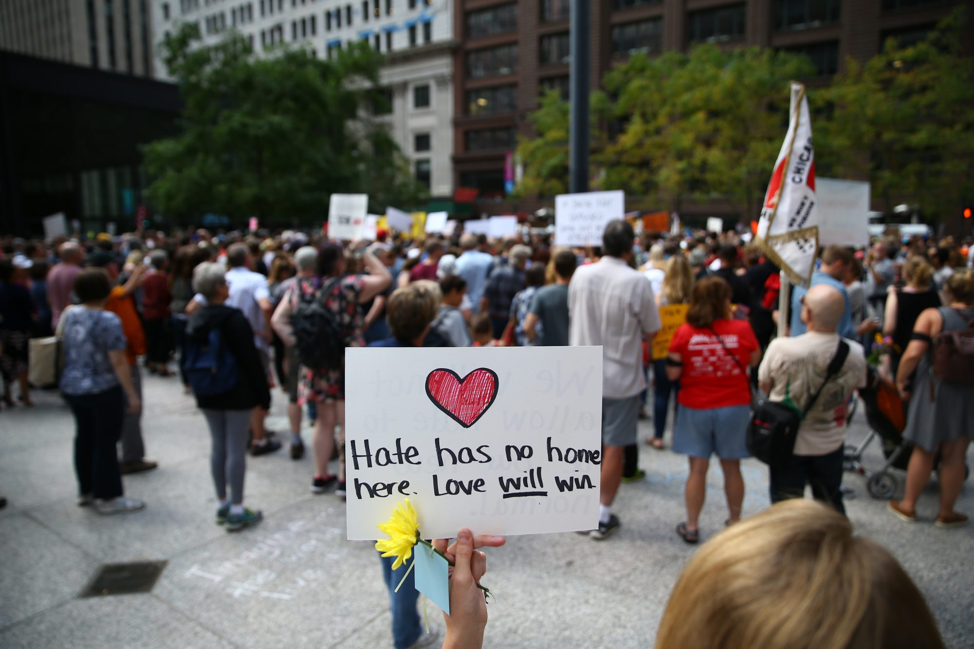 peaceful protesters hold love will win sign