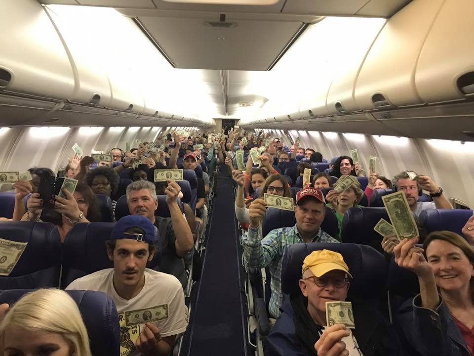 passengers holding up their two dollar bills