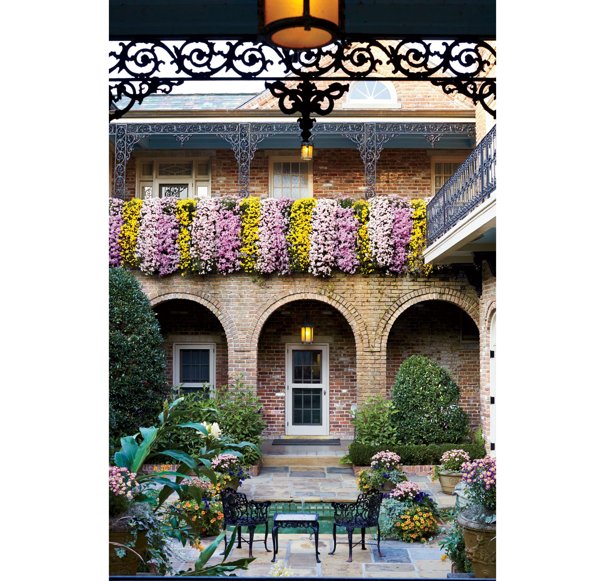 Multiple colors of cascade mums drape over the balcony of the historic Bellingrath Home