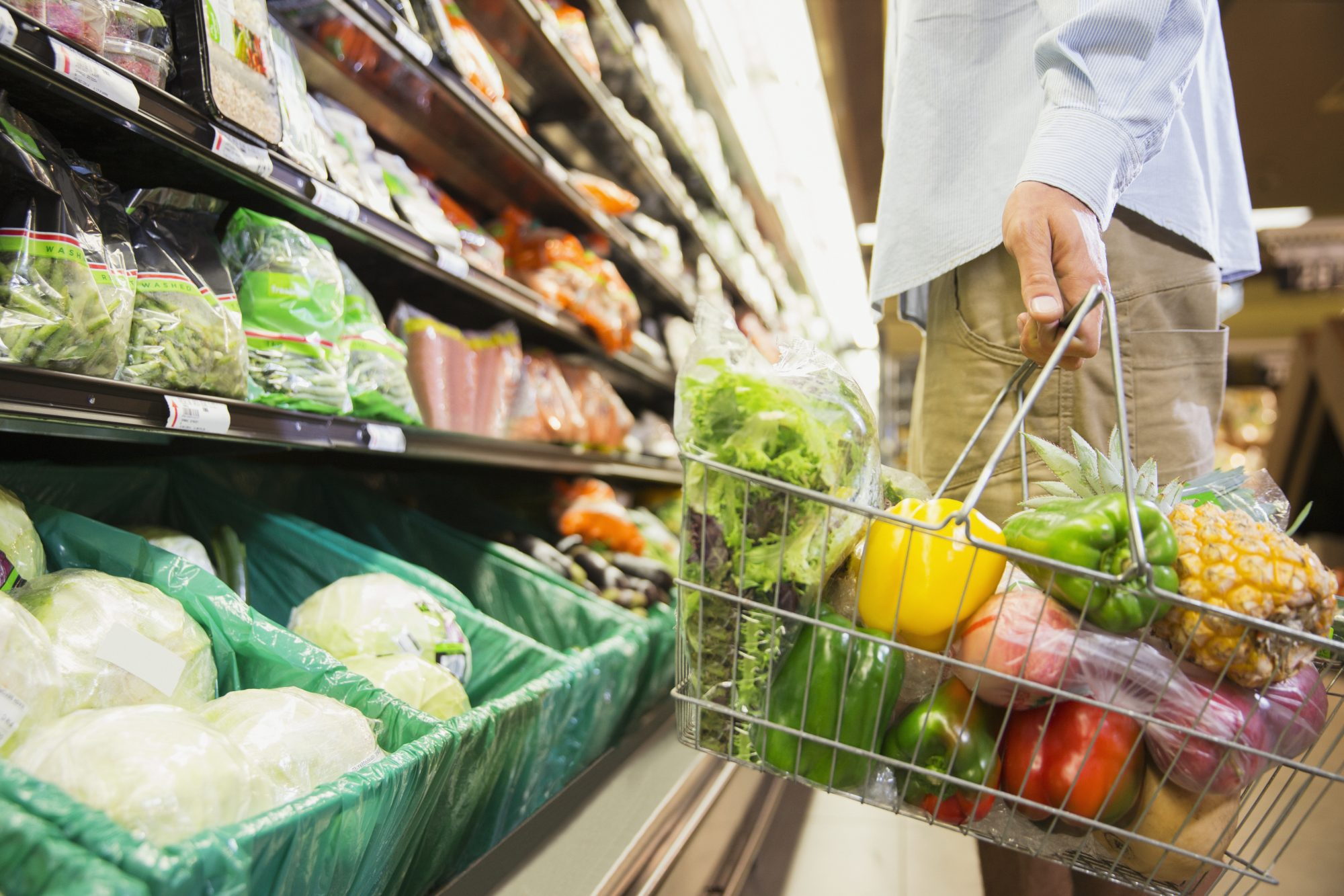 Man Holding Grocery Basket in Produce Section