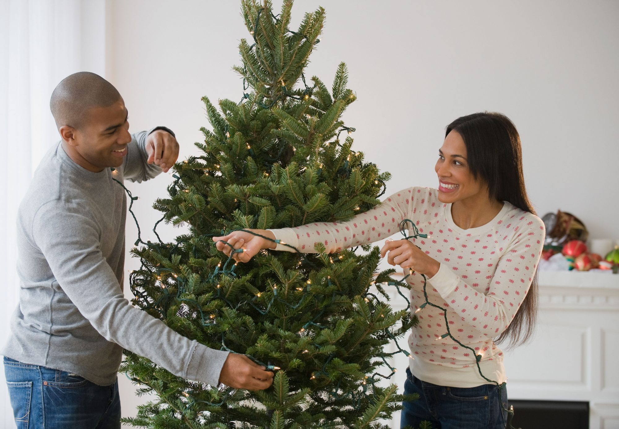 Couple Stringing Lights on Christmas Tree