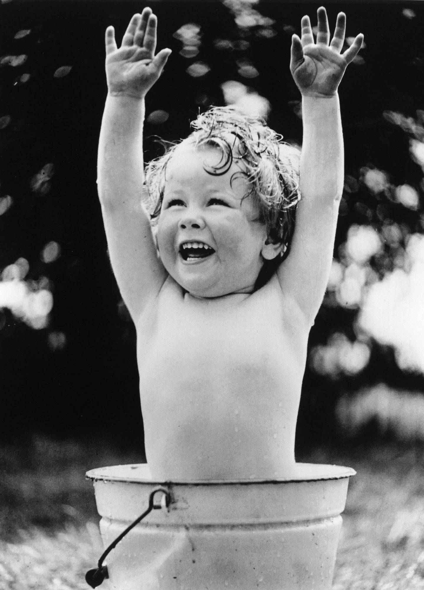Baby in Bucket with Hands Raised