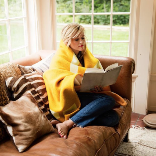 Reese Witherspoon Sitting on Couch Reading