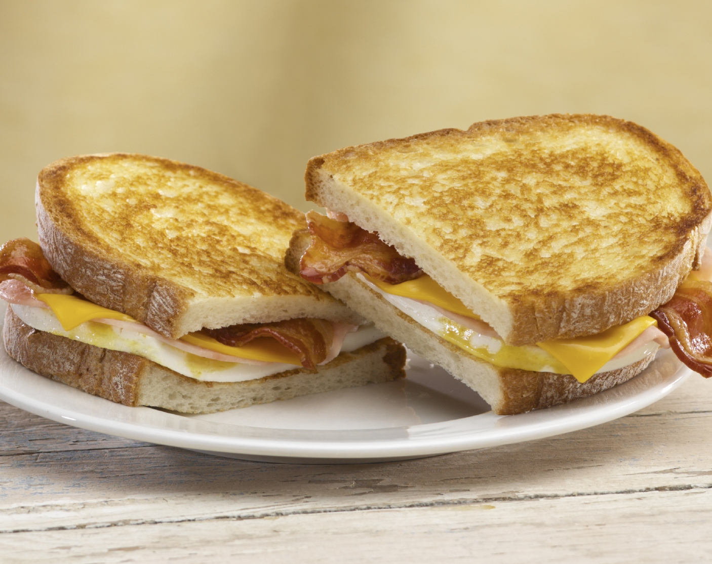 Grilled Breakfast Sandwich from Jack-in-the-box. With two freshly cracked eggs, two slices of ham, two strips of bacon and two slices of melting American cheese all on grilled artisan bread.