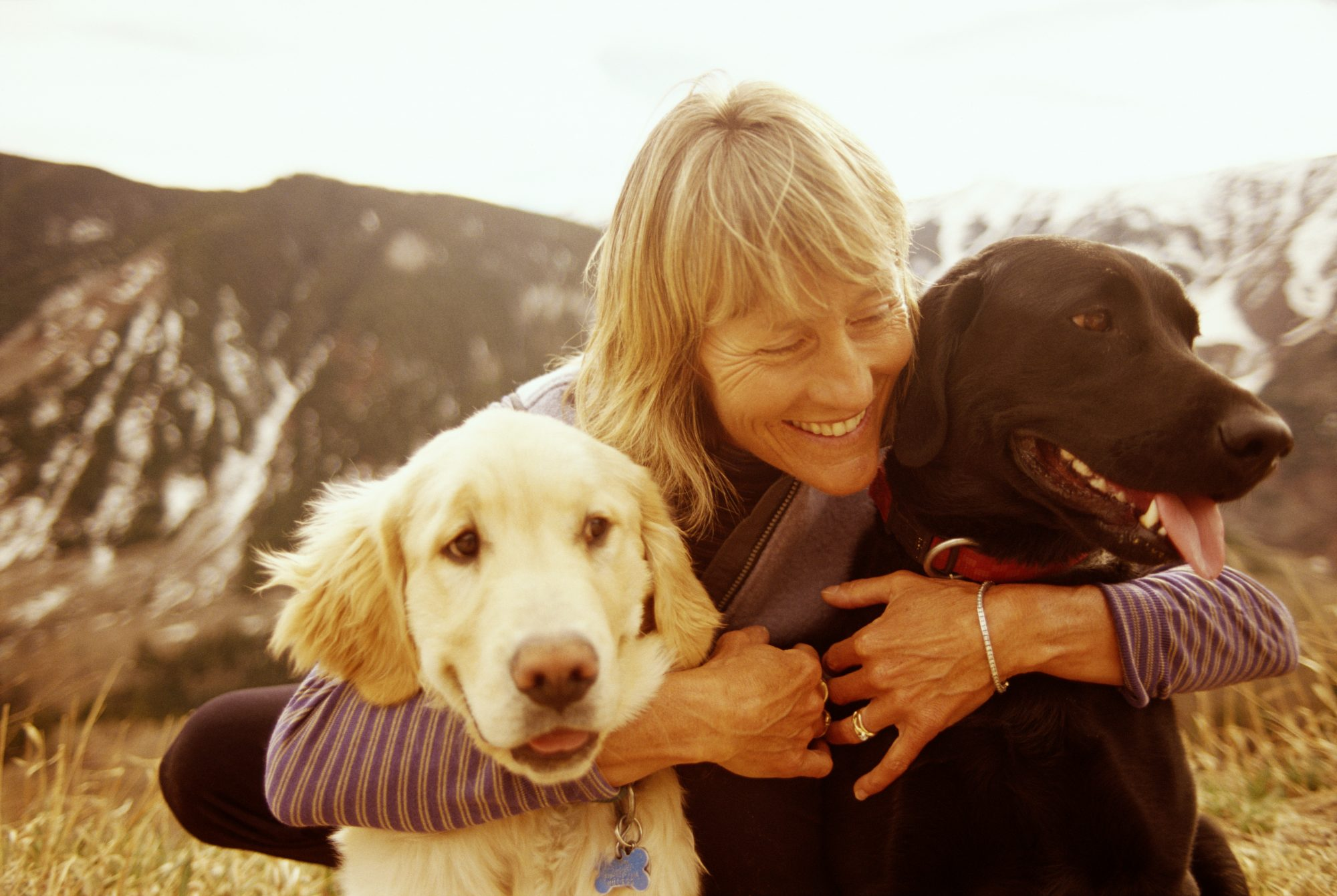 Woman Hugging Two Dogs