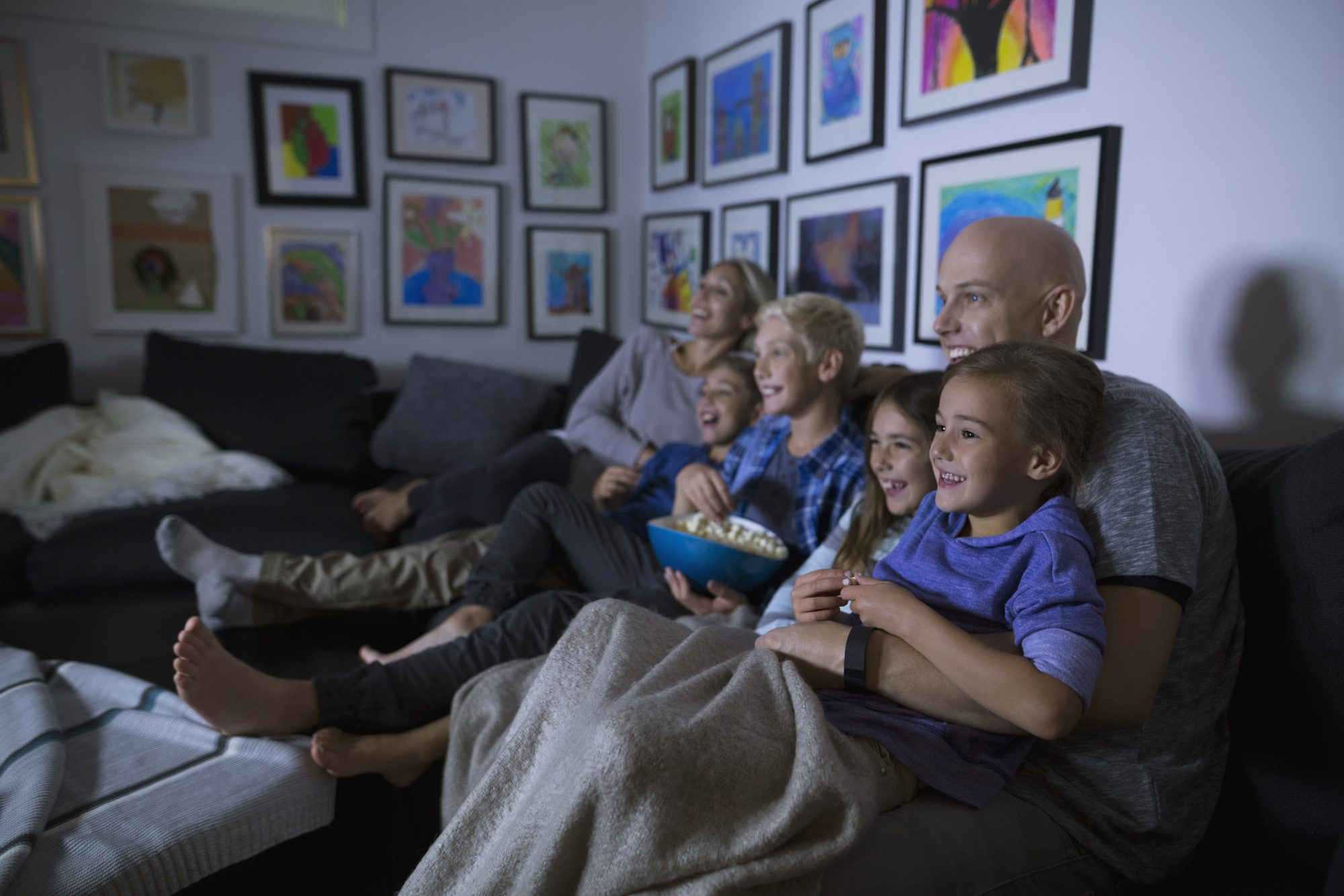 Family Watching TV on Couch with Popcorn