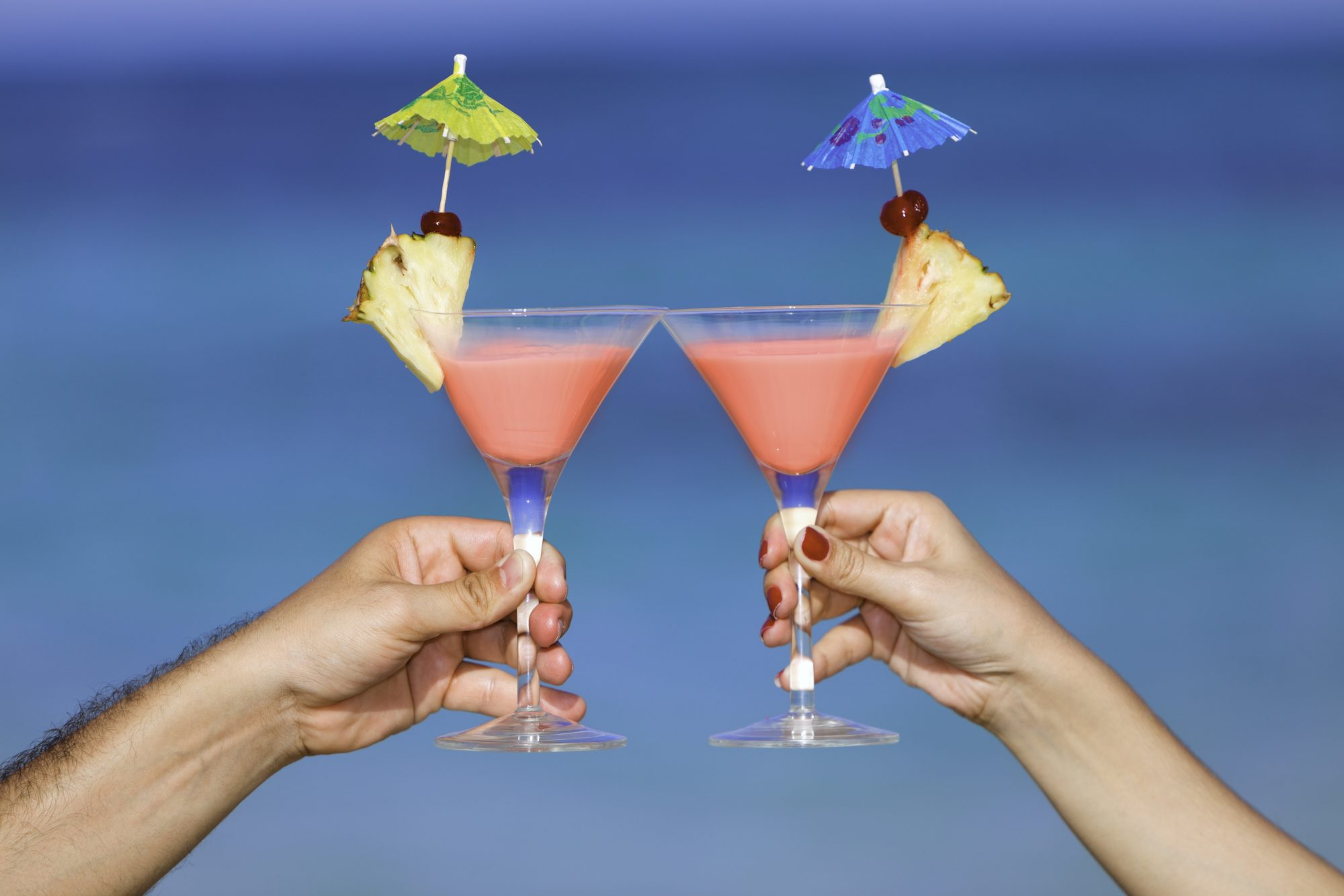 Couple toasting with tropical drinks on a turquoise beach