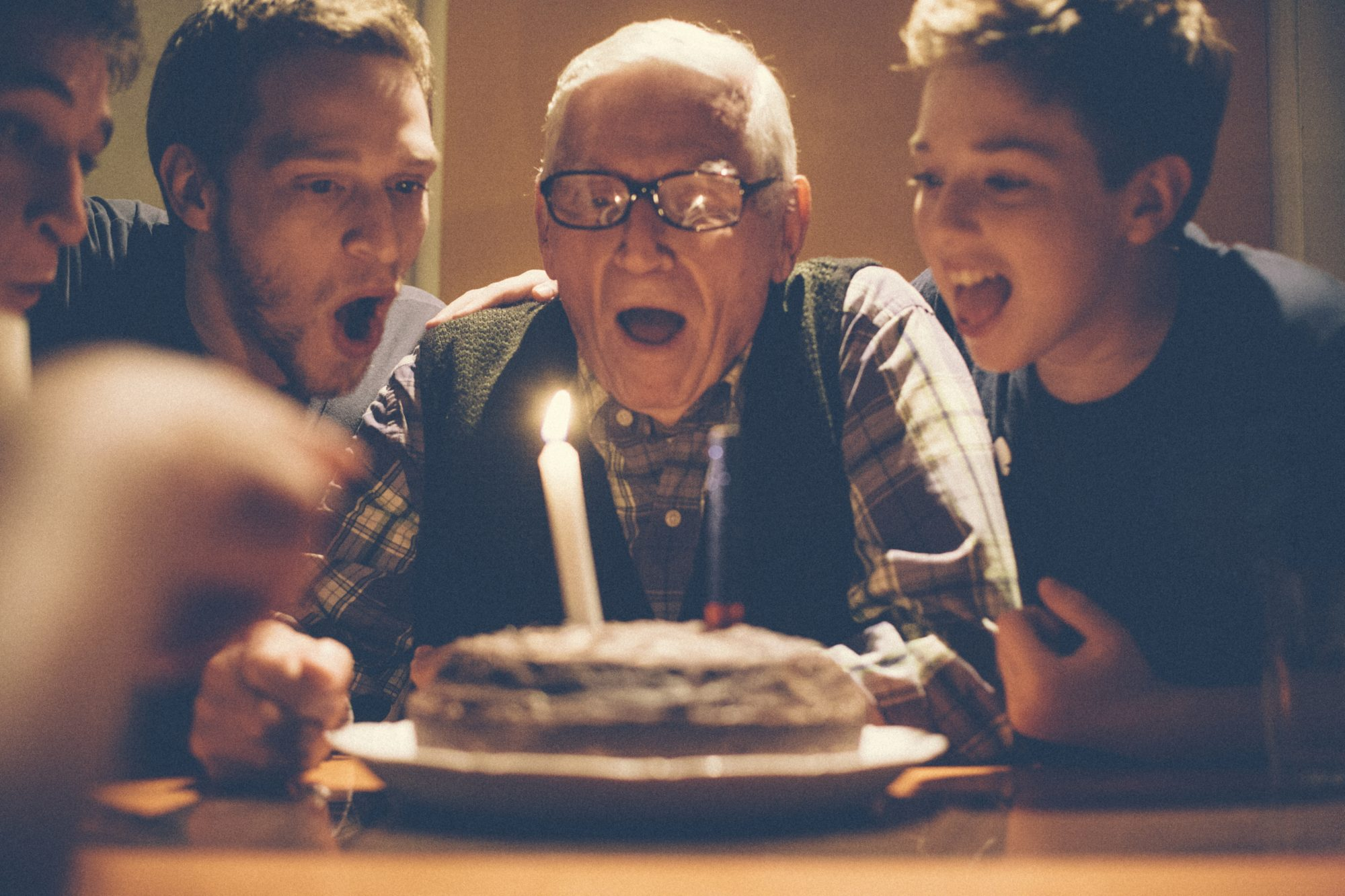 Young Men Celebrating Grandfathers Birthday Blowing Out Candles on Cake